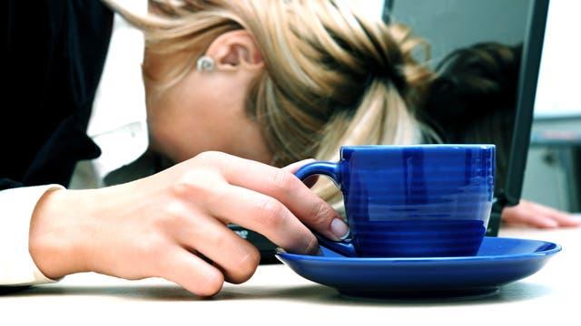 Frau sinkt trotz Kaffee auf ihrem Notebook zusammen