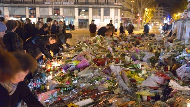 Duzende Menschen legen Blumen am Bataclan in Paris nieder, wo ein terroristischer Angriff eine große Zahl Opfer gefordert hat.