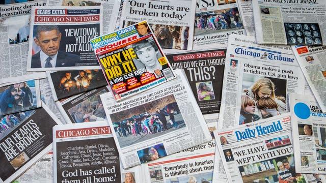 Zeitungen, deren Schlagzeilen sich mit Terror befassen, liegen ausgebreitet auf dem Boden.