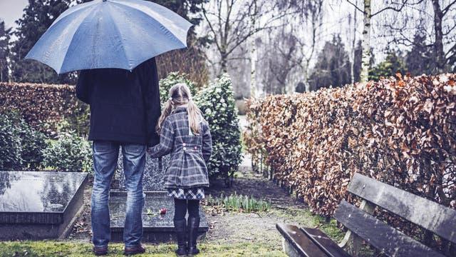 Ein Erwachsener und ein Kind stehen an einem Grab.