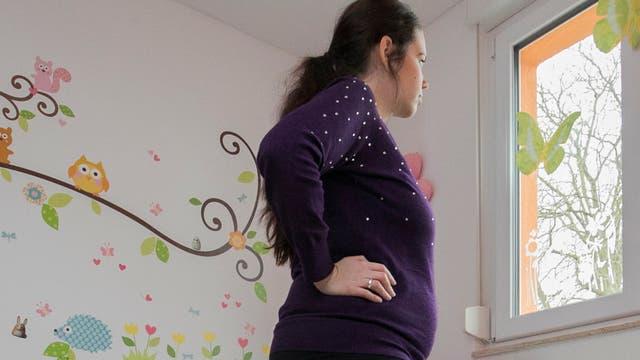 Eine schwangere Frau blickt aus einem Fenster. Sie befindet sich offenbar in einem Kinderzimmer.