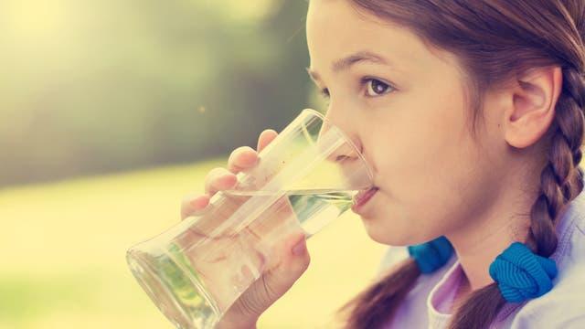 Ein Mädchen löscht seinen Durst mit einem Glas Wasser