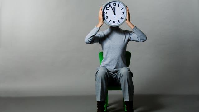 Auf einem Stuhl sitzt ein menschlicher Körper mit Uhr als Kopf.