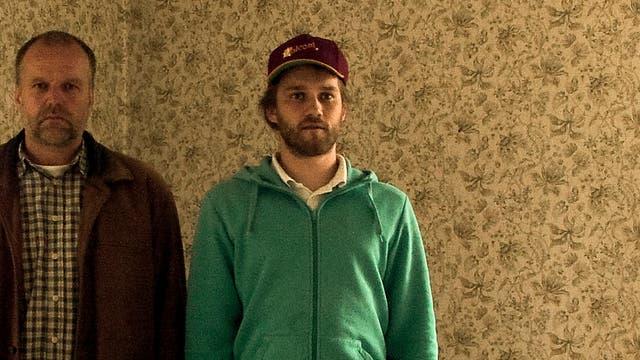 Vater und Sohn stehen in einem leeren Wohnraum, der von einer auffälligen alten Tapete geziert wird.