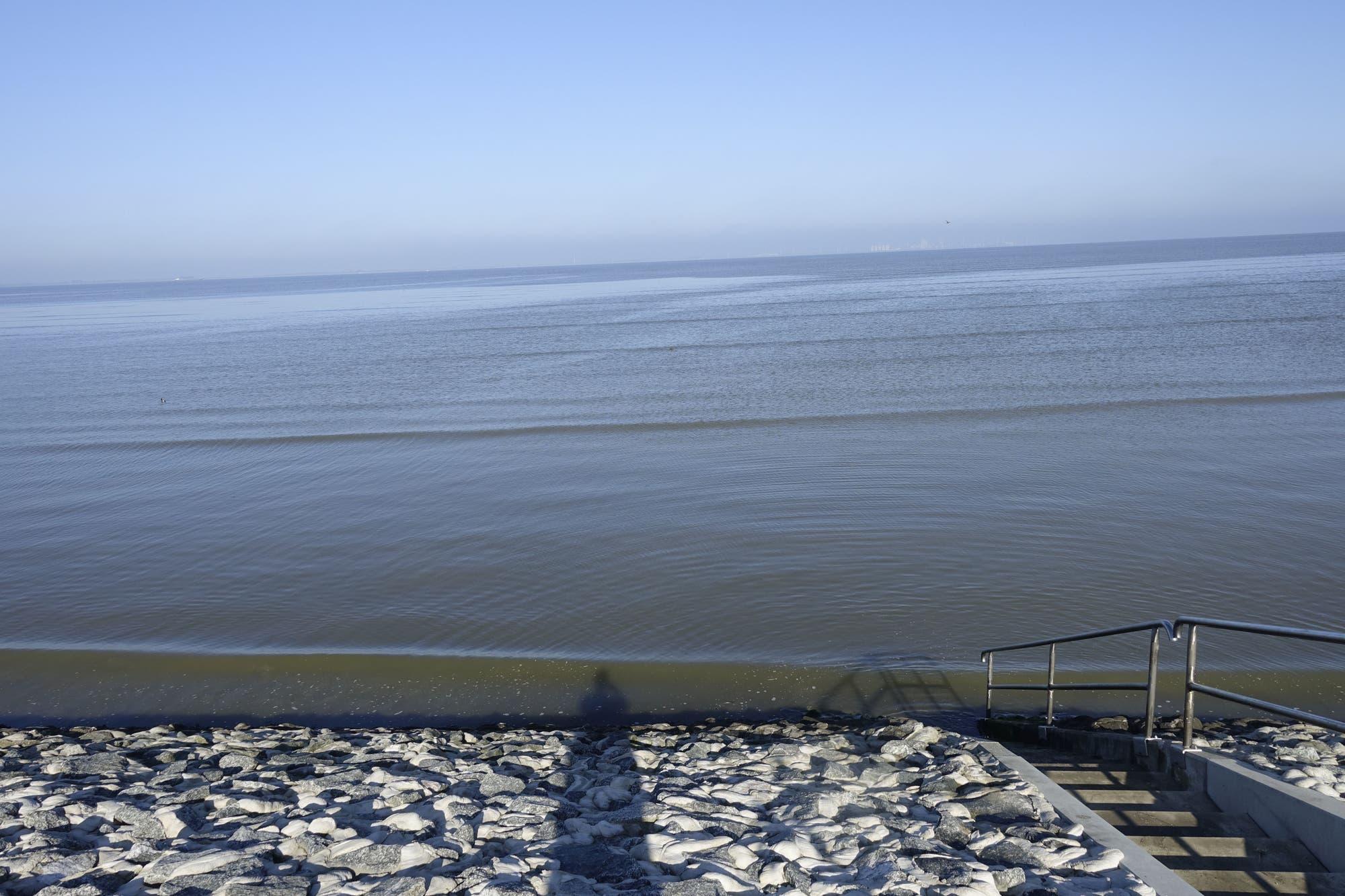 Foto von Wellenfronten, die über das Watt auf das Ufer zulaufen.