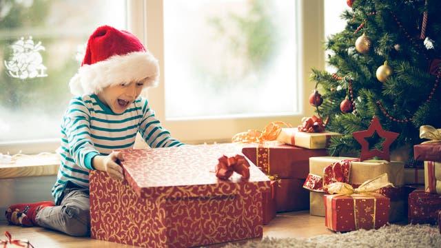 Eine fröhlicher Junge packt sein Geschenk aus