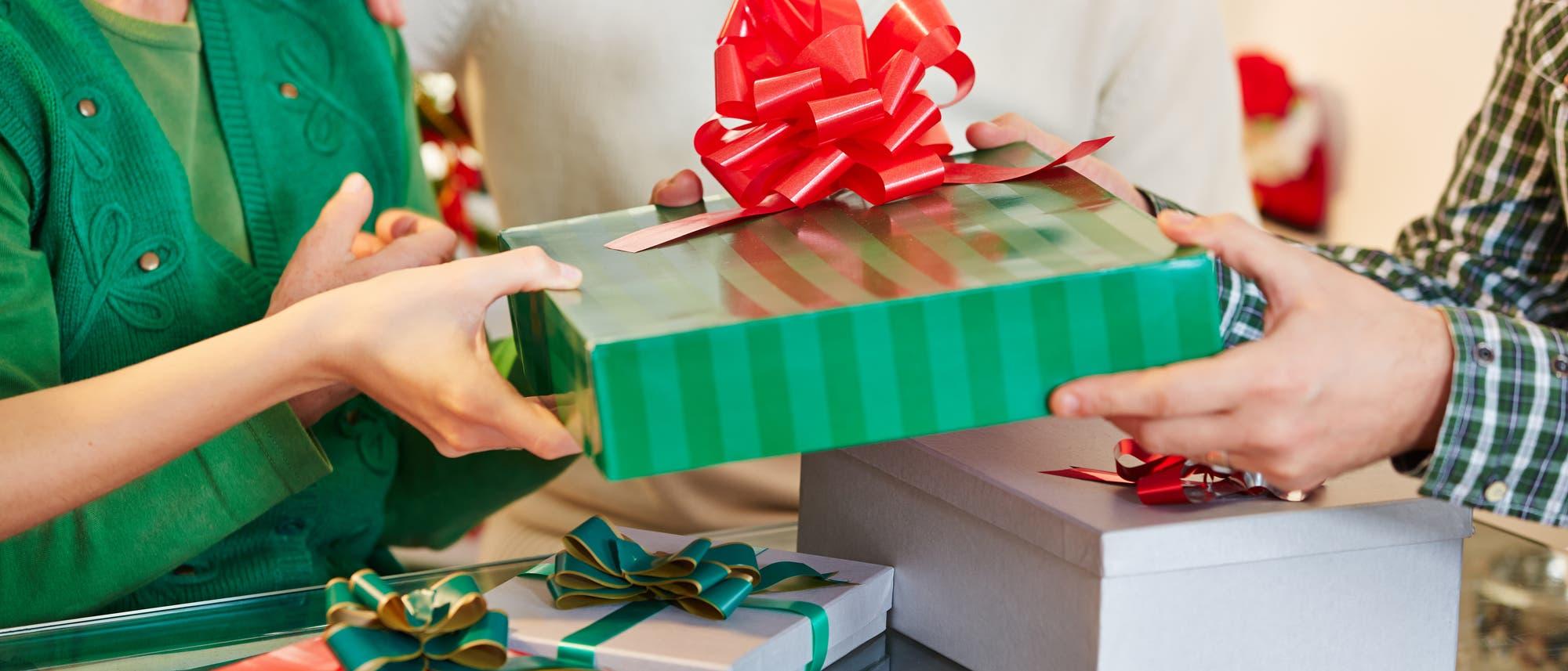 Zwei Menschen beschenken sich. Ein Mann übergibt einer Frau ein Geschenk.