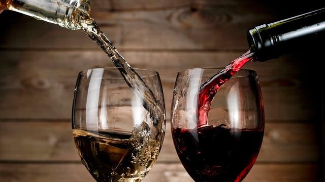 Rotwein und Weißwein werden aus der Flasche ins Glas eingeschenkt.