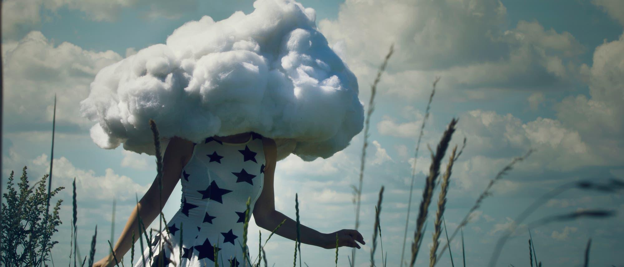 Eine Frau mit Wolkenkopf läuft durch ein Feld