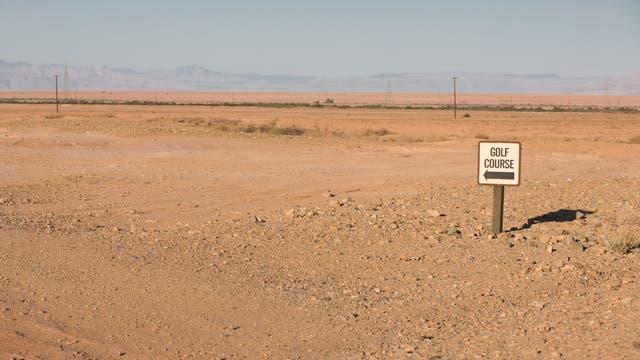 Schild weist auf einen Golfplatz in der Wüste hin