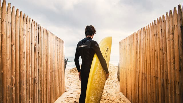 Ein Surfer mit seinem Board am Strand zwischen Palisaden.