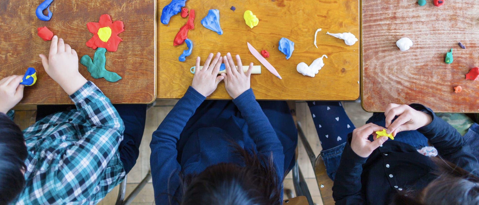 Kinder spielen im Kindergarten mit Knete.