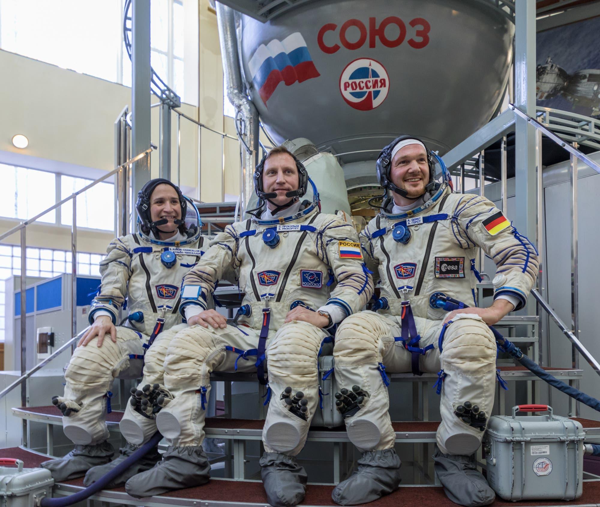 Neue ISS-Crew vor dem Reisegefährt
