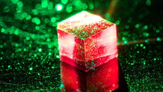 Ein würfelfürmiger Diamantkristall leuchtet rot unter grünem Laserlicht.