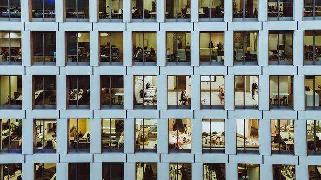 Menschen hinter Fenstern eines Bürogebäudes