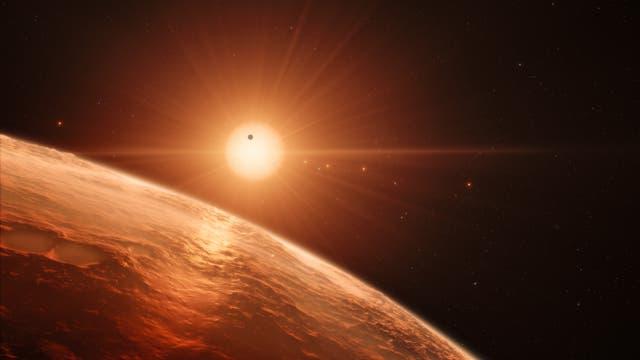 Sieben Welten um den roten Zwergstern TRAPPIST-1 (künstlerische Darstellung)