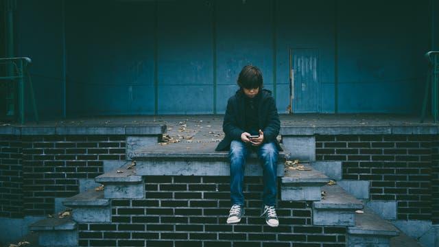 Ein Junge schaut auf sein Smartphone