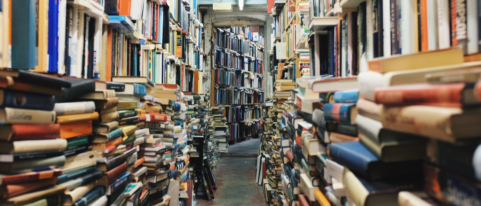 enger Gang zwischen gestapelten Büchern vor vollen Bücherregalen