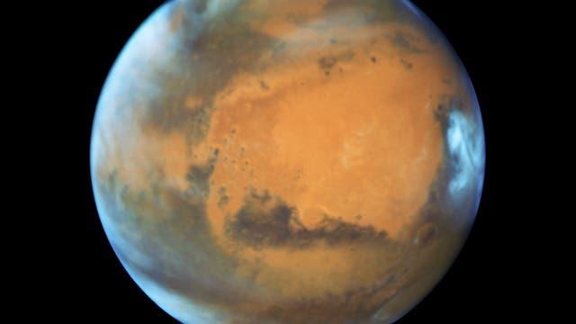 Eisbedeckte Polkappen, Wolken in der Atmosphäre, eine rostfarbene Landschaft, die von dunkleren Flecken durchsetzt ist. So präsentiert sich unser Nachbar auf diesem Bild, welches das Hubble-Weltraumteleskop am 12.Mai 2016 aufgenommen hat. Damals befand sich der Rote Planet in einer Entfernung von 50Millionen Kilometern zur Erde. Bemerkenswert sind vor allem die Eisschilde an Nord- und Südpol: Im Norden hat sich das Eis während des gegenwärtigen Marssommers weit zurückgezogen, während es im Süden weiter ausgedehnt ist. Dafür behindern dort Wolken die Sicht. Die große dunkle Region rechts ist Syrtis Major Planitia, die zu den ersten Oberflächenformationen gehört, die auf dem Mars entdeckt und beschrieben wurden- es handelt sich um einen alten und inaktiven Vulkan. Südlich davon schließt sich die die riesige Hellas Planitia an, die vor 3,5Milliarden Jahren durch einen Asteroideneinschlag entstand. Die orange Fläche im Zentrum wiederum ist Arabia Terra, ein ausgedehntes Hochland, das stark verkratert und erodiert ist.