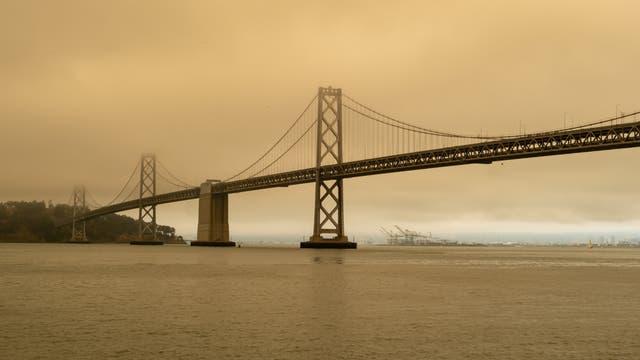 Die Bay Bridge in San Francisco umgeben von Smog durch nahe gelegene Waldbrände. Saubere Luft ist in der Ferne am Hafen von Oakland zu sehen.