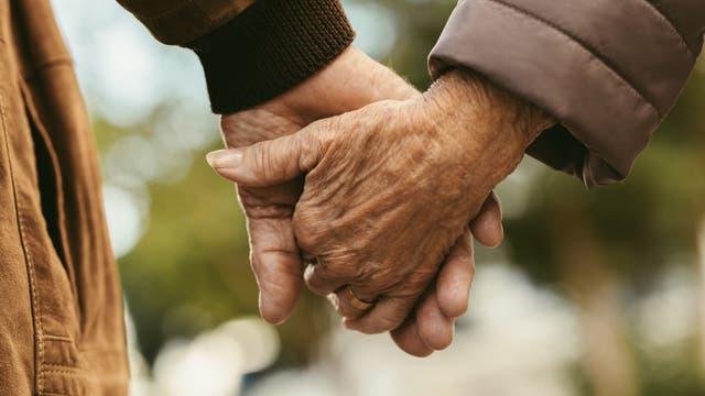 Zwei ältere Menschen halten sich an den Händen.