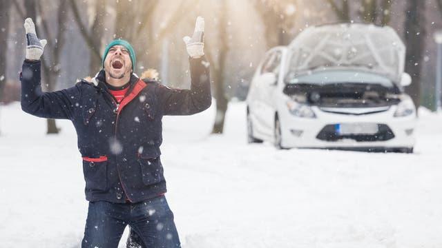 Ein Mann kniet im Schnee und verflucht das Universum. Im Hintergrund ein anscheinend defektes Auto.