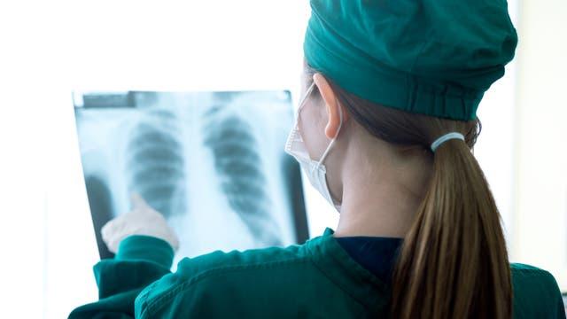 Ärztin begutachtet Röntgenbild einer menschlichen Lunge
