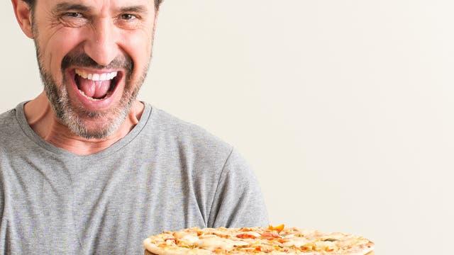 Ein Mann freut sich über die Pizza