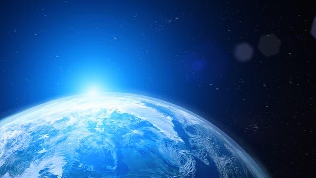 Eine Sonne steigt über den Rand eines erdähnlichen Planeten empor.