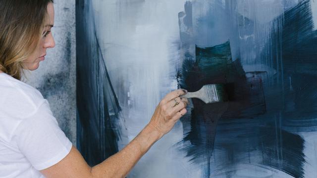 Traurige Frau streicht eine Wand schwarz