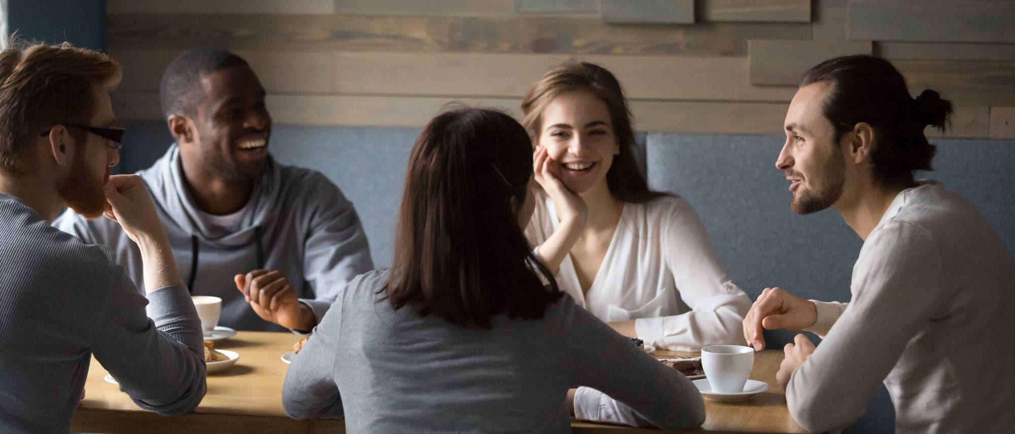 Eine Gruppe Freunde sitzt lachend und quatschend zusammen am Tisch