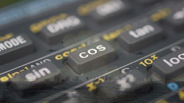 Nahaufnahme der Cosinus-Taste eines wissenschaftlichen Taschenrechners vor dem Hintergrund einer Atomexplosion über einer Stadt.