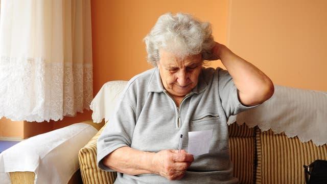 Eine ältere Dame schaut auf einen Zettel und scheint sich den Kopf zu reiben.