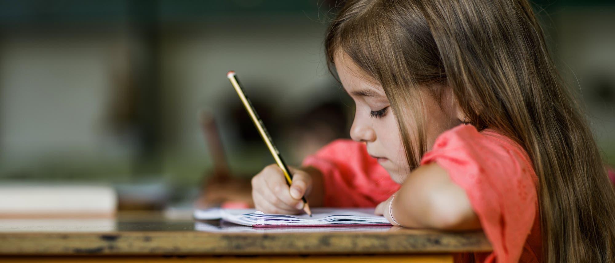 Ein kleines Mädchen schreibt an einem alten Pult in ein Heft