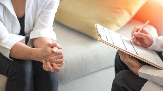 Arzt mit Klemmbrett und Fragebogen im Gespräch mit einem Patienten