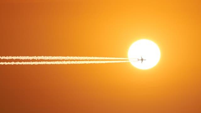 Ein Flugzeug mit Kondensstreifen vor der Sonne.