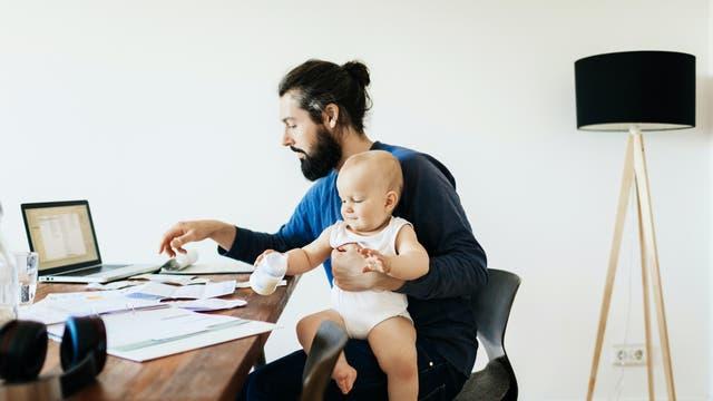Hipper Papa beim Arbeiten mit Baby auf dem Schoß