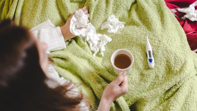 Eine Frau mit den üblichen Erkältungsutensilien: Decke, Tee, Taschentücher, Fieberthermometer.