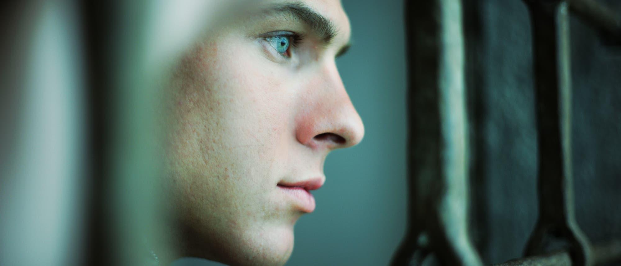 Ein Mann sieht zwischen den Gitterstäben eines Gefängnisses hervor.