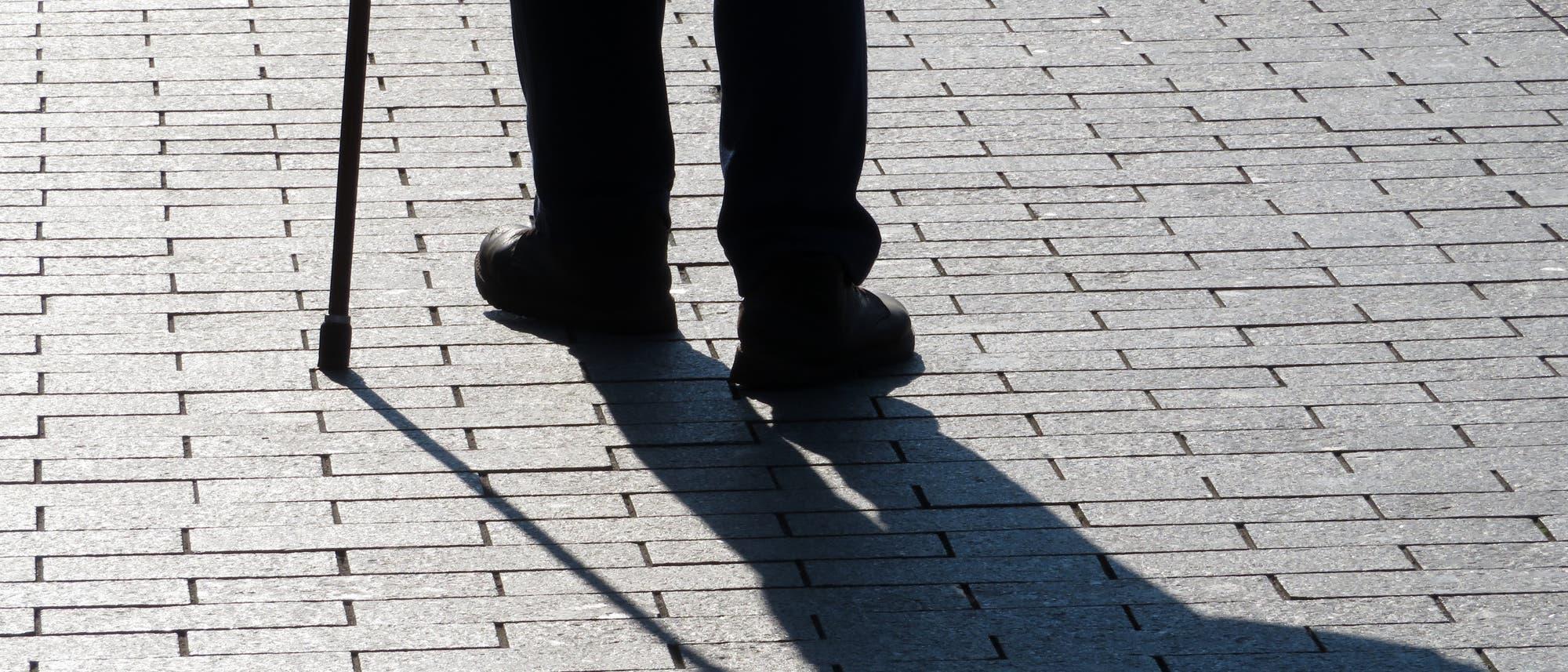 Silhouette und Schatten der Beine eines alten Mannes, der am Stock geht