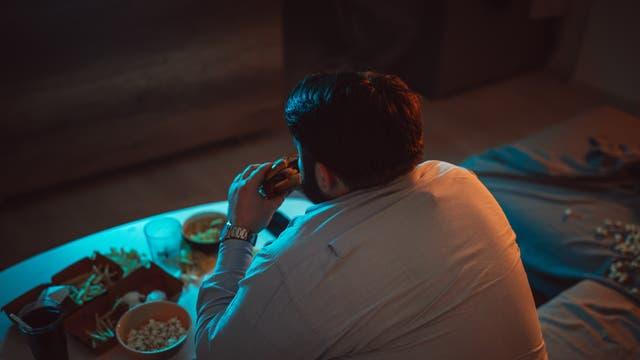 Übergewichtiger Mann isst alleine