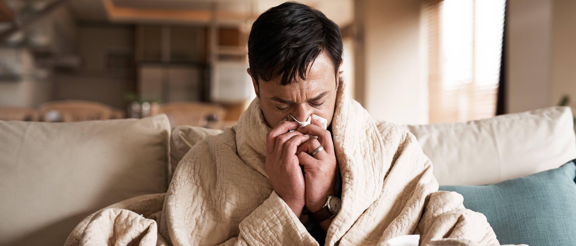 Ein Mann sitzt in eine Decke gehüllt auf der Couch und schneuzt sich die Nase.