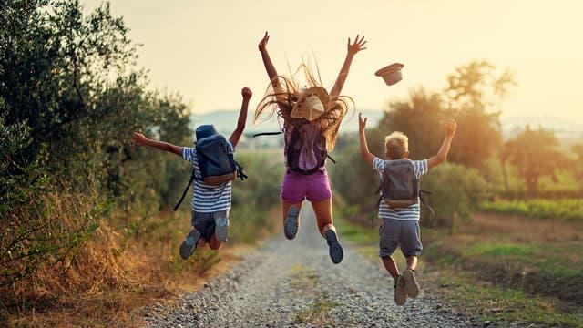 Kinder springen fröhlich in die Luft