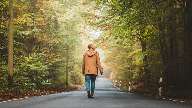 Ein Mann geht allein über eine Straße durch den Wald.