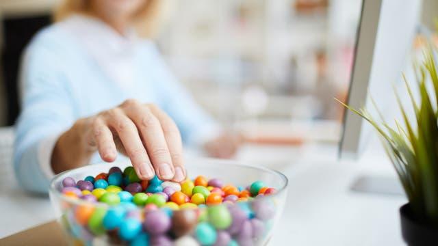 Frau greift in eine Schüssel voller Zuckerbonbons