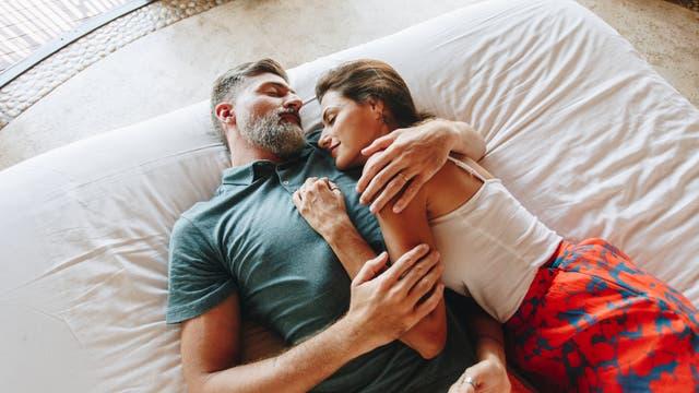 Ein Paar liegt glücklich auf dem Bett