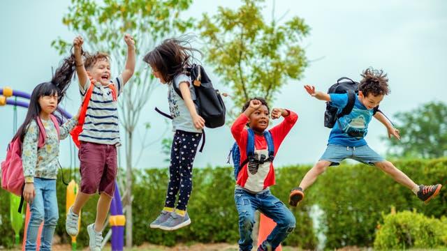 Mehrere Schulkinder beim Hüpfen auf einem Spielplatz.