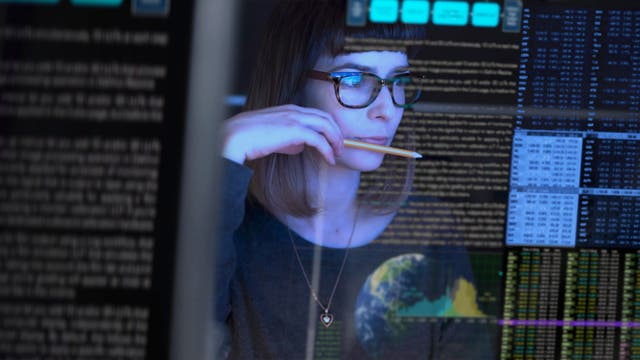 Junge Frau mit Brille studiert Datenreihen auf einem Bildschirm