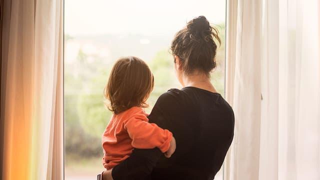 Frau und Kind blicken aus dem Fenster