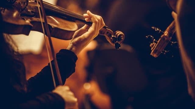 Frau mit Geige spielt in einem Orchester